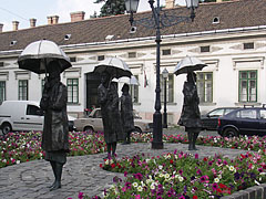 """Awaiting people"", life-size bronze statues of four female figures with umbrellas in their hands, in the old town of Óbuda - Budapešť, Maďarsko"