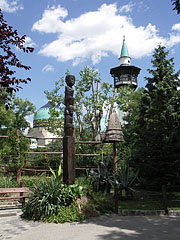 Wooden column-sculpture with African ground idols, and the Elephant House with its observation tower can be seen in the distance as well - Budapešť, Maďarsko