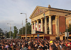 """The Hall of Art Budapest (""""Műcsarnok"""") in the light of the setting sun, as well as crow in front of it, gathering for a musical event - Budapešť, Maďarsko"""