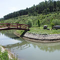 Small lake with wooden bridge and prehistoric rhinos - Ipolytarnóc, Maďarsko