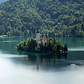 Tiny island with a church in the middle of the beautiful deep green Bled Lake, viewed from the castle - Bled, Slovenya