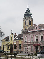 Shops on the main square with the tower of the Roman Catholic church in the background - Szentgotthárd, Macaristan