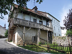 An old crumbling two-storey house on the steep winding street, with a timer porch on upstairs - Slunj, Croazia