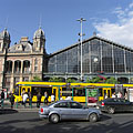 A yellow Combino tram in the stop in front of the Nyugati Railway Station - Budapest, Ungarn