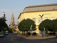 The yellow Town Hall building of Rákospalota neighborhood, as well as the Roman Catholic Parish Church in the distance - Boedapest, Hongarije