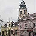 Shops on the main square with the tower of the Roman Catholic church in the background - Szentgotthárd, Hongarije