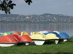 Pedal boats on the lakeshore, and on the other side of the Velencei Lake these are the houses of Sukoró village on the hillside - Agárd, Hungary