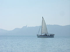 "The ""Őszöd"" sailboat is in front of the silhouette of the Benedictine Abbey in Tihany - Balatonfüred, Hungary"