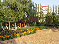 """Flowered park, and further away the """"Tulipán House"""" (""""Tulip House"""") holiday resort in the Napospart Street can be seen - Balatonlelle, Hungary"""