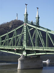 "The Pest-side tower (pylon) of the Liberty Bridge (""Szabadság híd"") in front of the Gellért Hill - Budapest, Hungary"