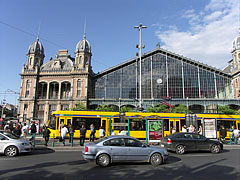 A yellow Combino tram in the stop in front of the Nyugati Railway Station - Budapest, Hungary