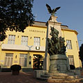 "The Town Hall (""Városháza"") of Rákospalota, and a World War I monument in front of it, with a legendary turul bird on its top - Budapest, Hungary"