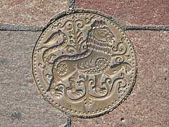 A circular bronze piece of art, a lion figure in the pavement - Esztergom, Hungary