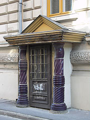 A small side entrance on the City Hall building, there are purple glazed ceramic columns and a tympanum around the door - Hódmezővásárhely, Hungary