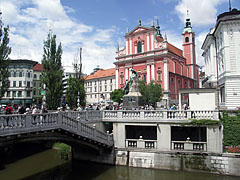 "The Triple Bridge (""Tromostovje"") over the Ljubljanica River and the reddish Franciscan Church on the Prešeren Square, viewed from the colonnade of the Plečnik's arcades - Ljubljana, Slovenia"