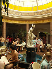 Statue of a bathing woman on a fountain in the dome hall of the bath, surrounded by restaurant tables - Miskolc, Hungary