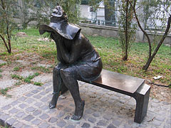 """Under the hat"", bronze statue of a female figure with a hat and sitting on a bench, on the riverside promenade by the Tisza River - Szeged, Hungary"